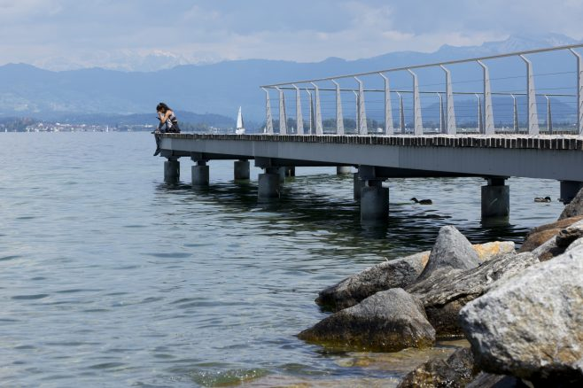 pretty girl sitting at the side of Lake Zurich